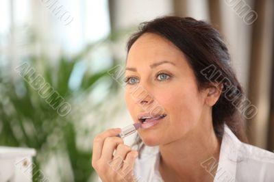 brunette putting on mauve lipstick