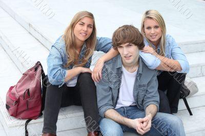 Three teenage friends sat on steps