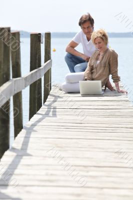mature couple with laptop seated on pontoon