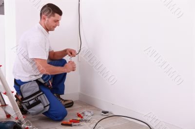 Male electrician preparing length of wire