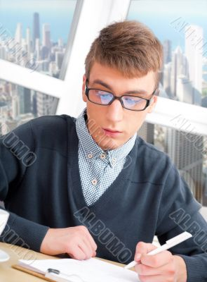 Young male student doing homework in his room at home