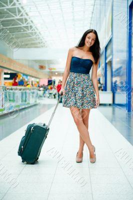 """Young pretty stylish woman with luggage at the internati""""li"""