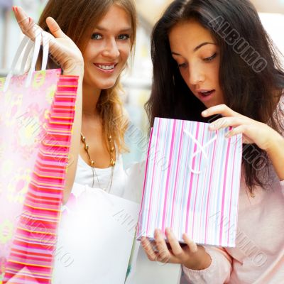 Two excited shopping woman resting on bench a