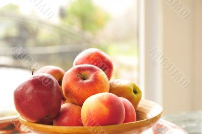 Closeup photo of red apples on wooden plate indoor against wide