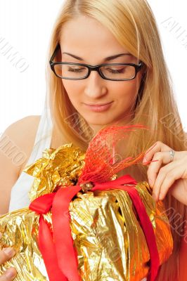Beautiful student woman holding a gift isolated on white
