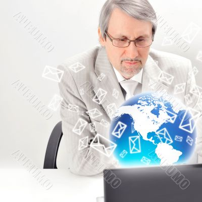 Portrait of an older businessman with a computer and a cup.