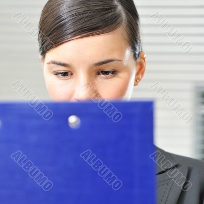 A portrait of a young business woman in an office with documents