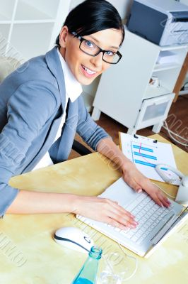 Beautiful business woman smiling while working with reports and
