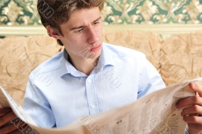 Closeup portrait of young man with newspaper