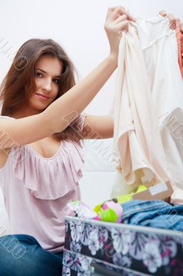 Beautiful young slim woman on the bed indoors unpacking clothes