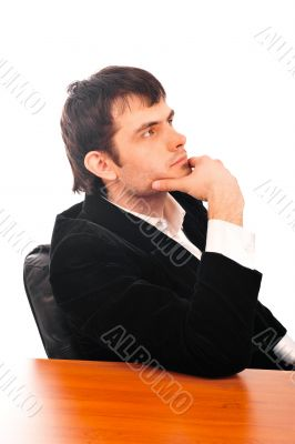 Portrait of a happy young businessman in suit sitting at office