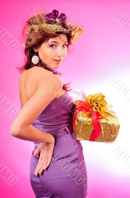 Cute smiling girl holding the golden box with red tape present o