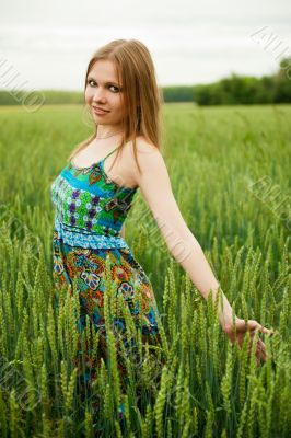 Portrait of young woman stands in a field of