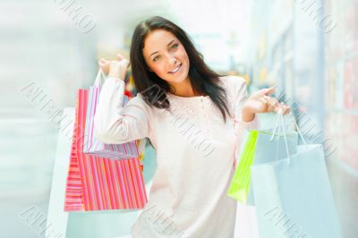 Photo of young joyful woman with shopping bags on th
