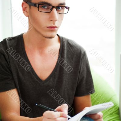 Young adult man writing in his copybook while sitting on a large