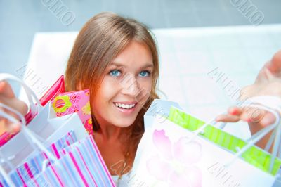 Shopping woman with lots of bags smiles inside mall. She is happ