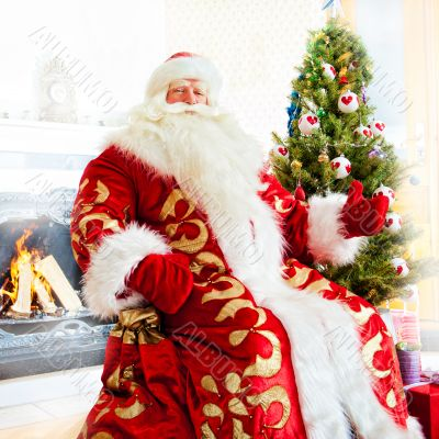Santa sitting at the Christmas tree, fireplace and looking at ca