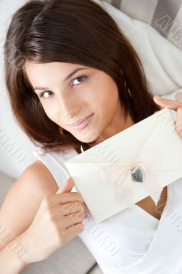 Delighted woman reading a valentine greeting card with heart and