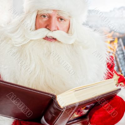 Santa sitting at home and reading a book. Indoors
