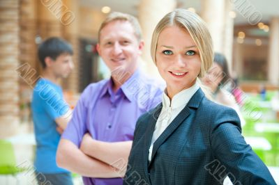 Portrait of a cute business woman with colleagues at the backgr