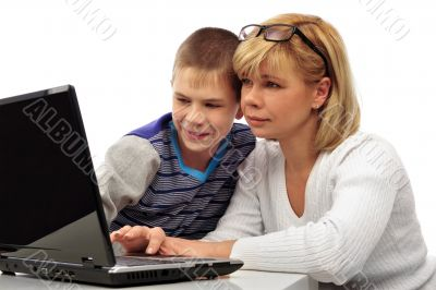 Portrait of adult woman watching as her son doing homework