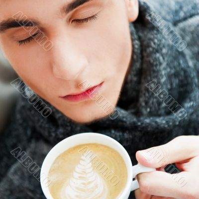 Portrait of a young man drinking coffee while sitting on armchai