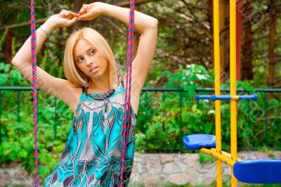 Portrait of pretty young woman swinging on playground at park an