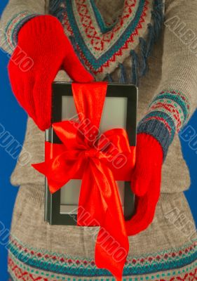 Girl holds electronic book reader with red gloves