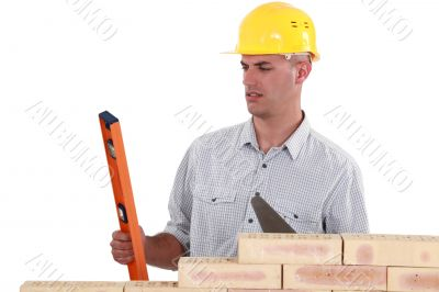 mason holding a level and a trowel