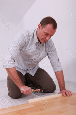 handyman laying  a laminate parquet