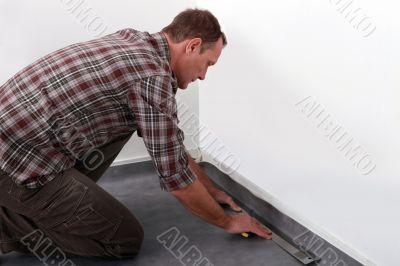 Tradesman laying down linoleum flooring