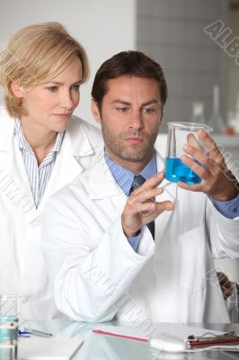 Man and woman in white laboratory coats, examining blue liquid
