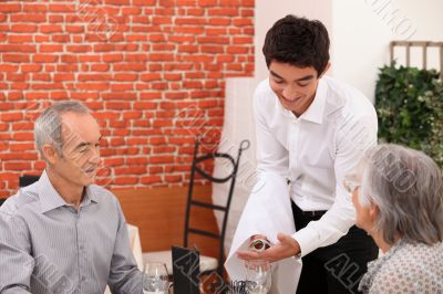 Young waiter pouring wine for an older couple