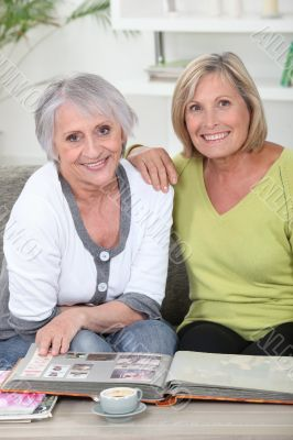 duo of mature women skimming through album