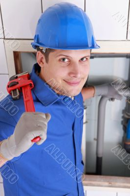 Plumber installing pipes with a large wrench