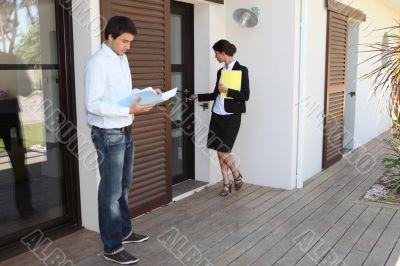 man and female realtor near house