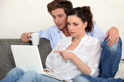 Man with coffee and woman in front of notebook