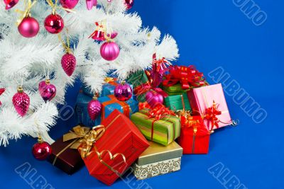 Heap of the Christmas presents under decorated white evergreen t