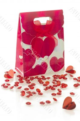 Red gift bag with heart pattern and bow, isolated on white background