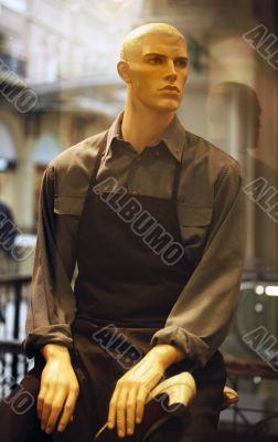 Dummy in working clothes in a show-window of a boutique