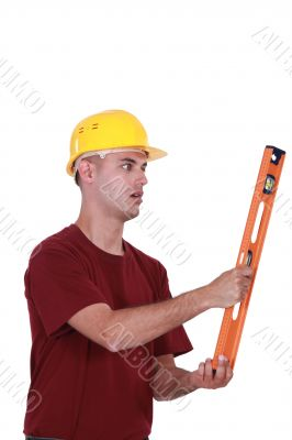A manual worker with a level.