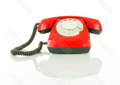Red old fashioned telephone against white background