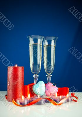 Two wineglasses and burning candles against blue background