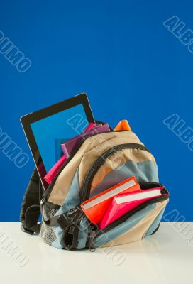 Backpack with colorful books and pablet PC on the blue backgroun