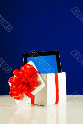 Tablet PC in a gift box against blue background