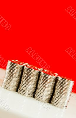 Coins stacked in bars against red background