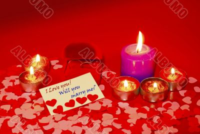 Two rings and a card with marriage proposal with six candles