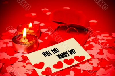 Card with marriage proposal and two rings and two candles