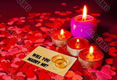 Two rings and a card with marriage proposal with four candles