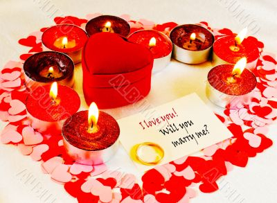 Ring and a card with marriage proposal with candles